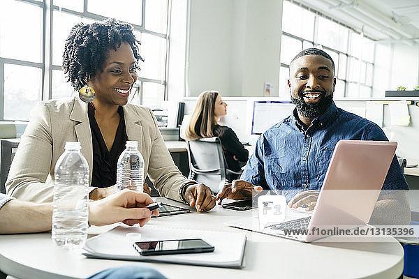 Geschäftsleute betrachten Laptop-Computer im Büro
