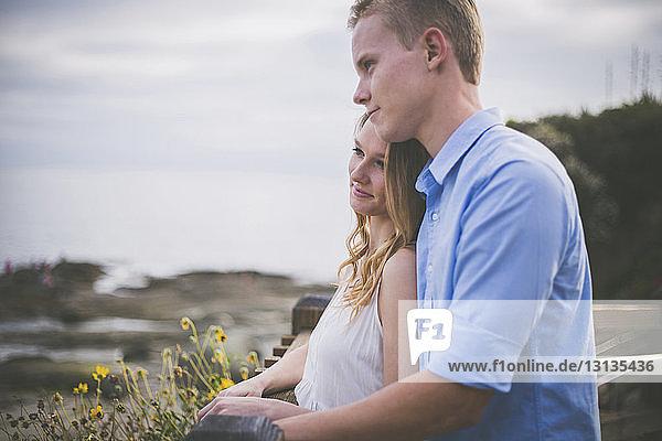 Lächelndes Paar schaut weg  während es am Geländer vor bewölktem Himmel steht