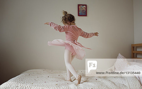 Girl in ballet costume dancing on bed at home