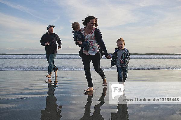 Fröhliche Familie läuft am Strand an Land