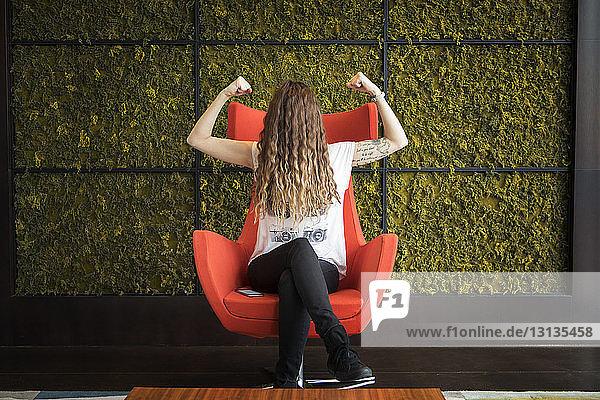 Frau mit Haaren im Gesicht  die Muskeln beugt  während sie zu Hause auf einem Sessel an der Wand sitzt