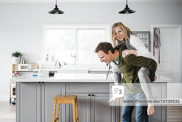 Portrait of smiling woman piggybacked by man in kitchen at home