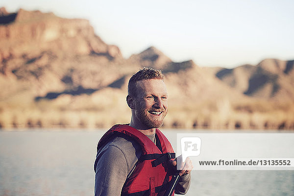 Happy man wearing life jacket against lake and mountain