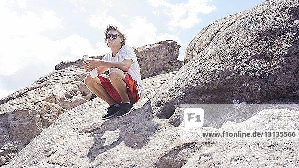 Mann mit Wasserflasche kauert auf einem Felsen vor klarem Himmel