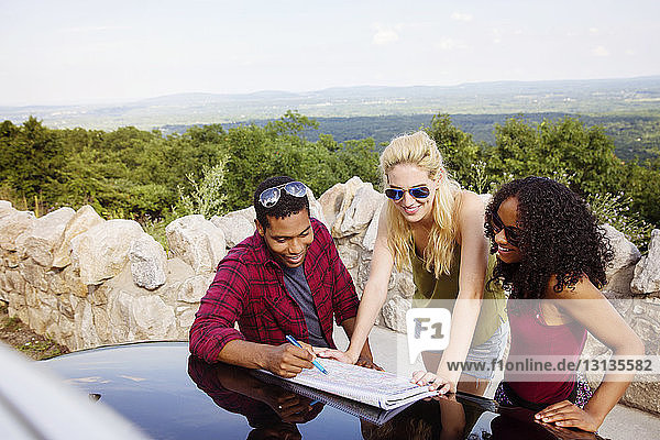 Friends planning trip on map during vacation with landscape in background