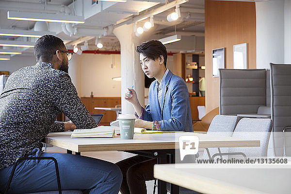 Businesswoman discussing with male coworker in office