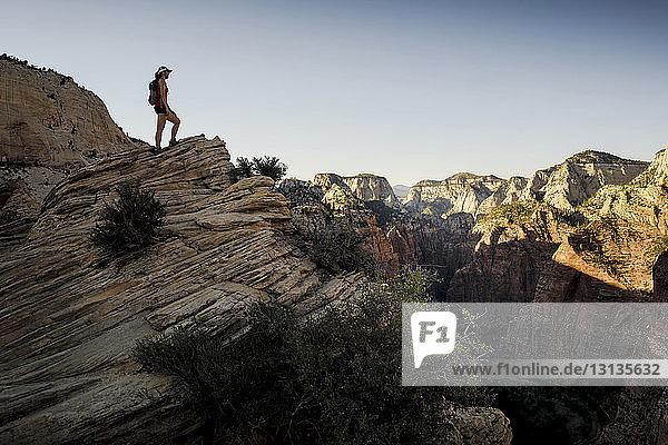 Wanderer steht auf einer Felsformation und blickt in den klaren Himmel