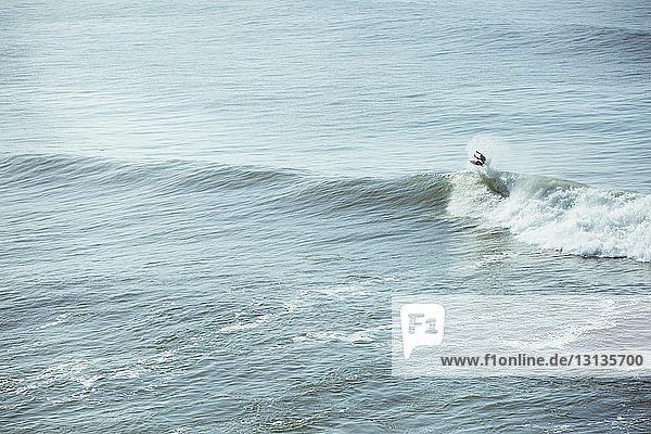 Mann surft auf einer Welle im Meer