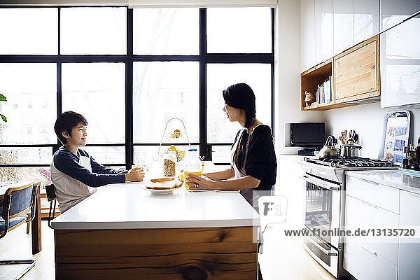 Mother and son eating breakfast on table at brightly lit kitchen