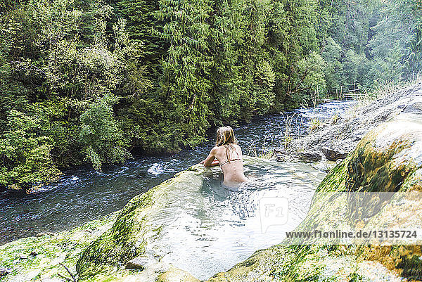 Rear view of woman swimming in hot spring by stream at forest