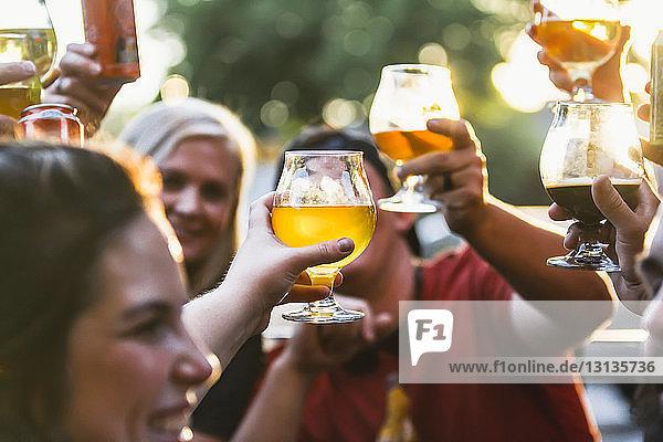 Glückliche Freunde stoßen in einer Bar auf Bier an