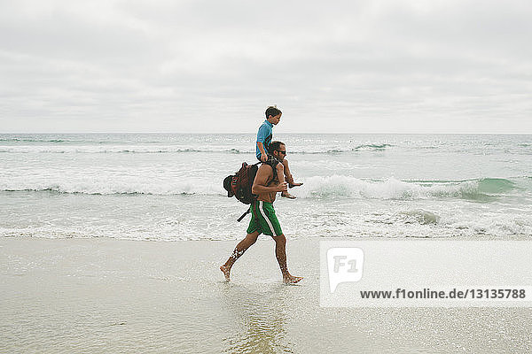 Father carrying son on shoulders while walking against sky at beach