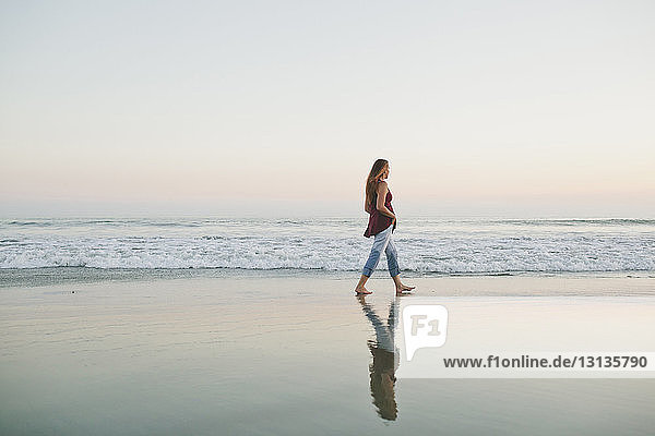 Full length of woman walking on shore against sea and clear sky during sunset