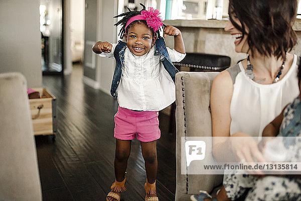 Porträt eines glücklichen Mädchens  das gestikulierend bei seiner Familie zu Hause steht