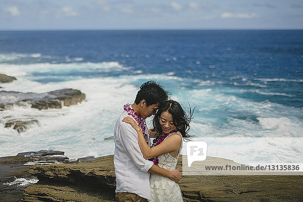 Romantisches Paar steht am Strand gegen den Himmel