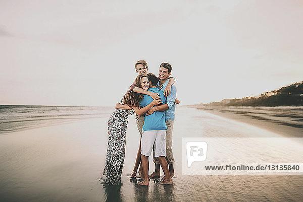 Glückliche Geschwister umarmen sich  während sie bei Sonnenuntergang am Strand gegen den Himmel stehen