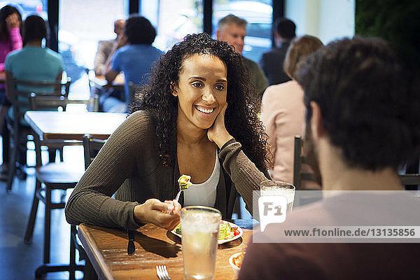 Frau sitzt mit Mann beim Essen im Restaurant