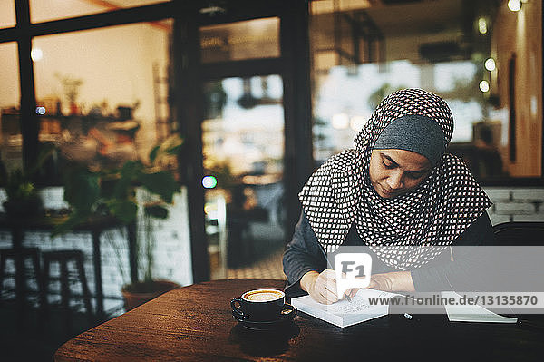 Woman writing in book at coffee shop