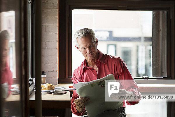 Reifer Mann liest Zeitung bei Kaffee und Croissant im Café