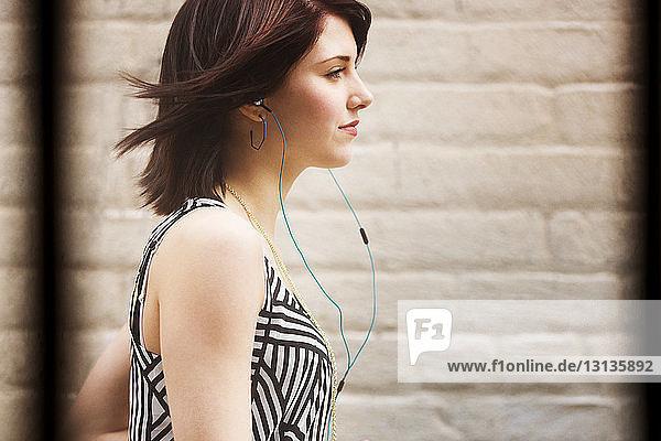 Seitenansicht einer Frau  die Kopfhörer trägt und gegen eine Wand läuft