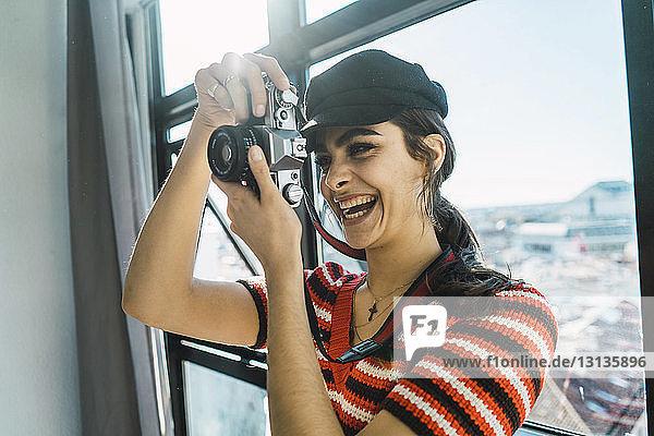 Fröhliche junge Frau fotografiert mit der Kamera  während sie zu Hause vor dem Fenster steht