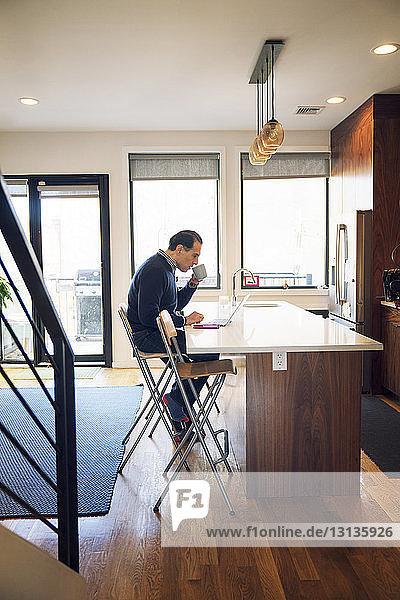 Seitenansicht eines Mannes  der einen Laptop-Computer benutzt  während er zu Hause am Tisch Kaffee trinkt