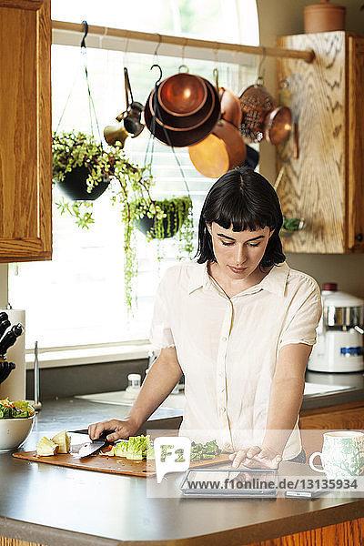 Frau liest digitale Tablette  während sie zu Hause in der Küche frisches Gemüse schneidet