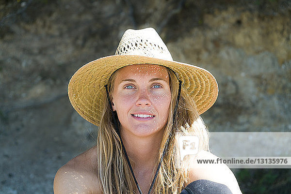 Close-up portrait of woman in sun hat at beach