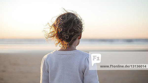 Rear view of girl standing at beach against sky during sunset