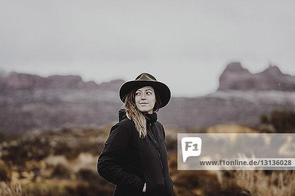 Frau mit Hut schaut weg  während sie in der Wüste gegen den Himmel steht