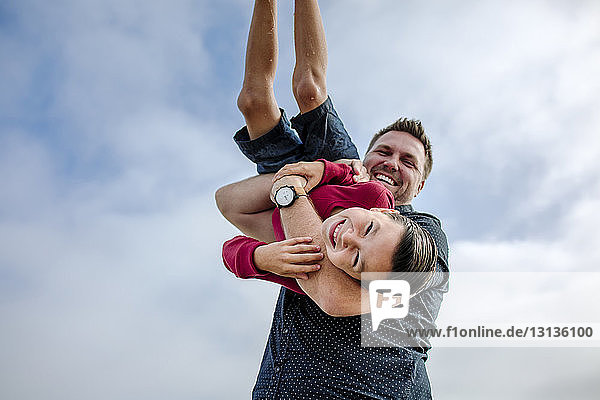 Low angle portrait of cheerful father lifting smiling son against cloudy sky