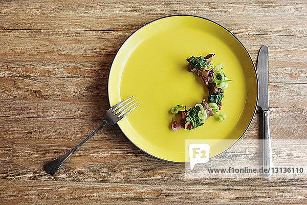 Draufsicht auf den Salat mit Messer und Gabel auf dem Tisch
