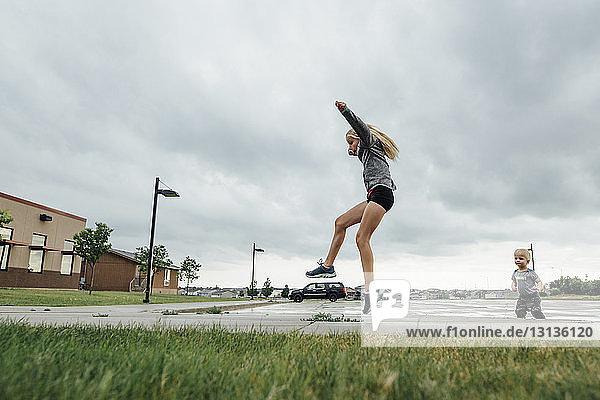 Kleiner Junge sieht Schwester an  die auf der Straße gegen bewölkten Himmel springt