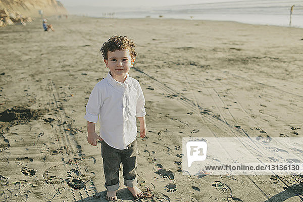 High angle portrait of cute boy standing at beach during sunny day