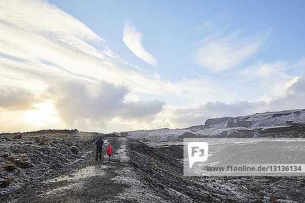 Rückansicht eines Vaters mit Tochter beim Spaziergang durch die Landschaft vor bewölktem Himmel bei Sonnenuntergang