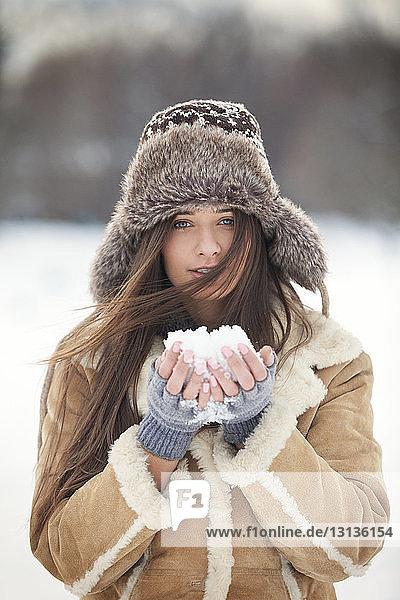 Porträt einer schönen Frau in warmer Kleidung  die Schnee hält