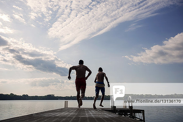 Rear view of father and son running on pier at lake