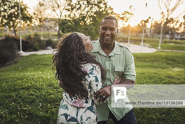 Glückliches Paar steht auf dem Spielfeld im Park