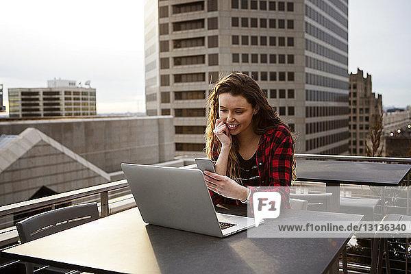Junge Frau  die ein Smartphone benutzt  während sie mit ihrem Laptop auf einem Tisch im Terrassencafé sitzt