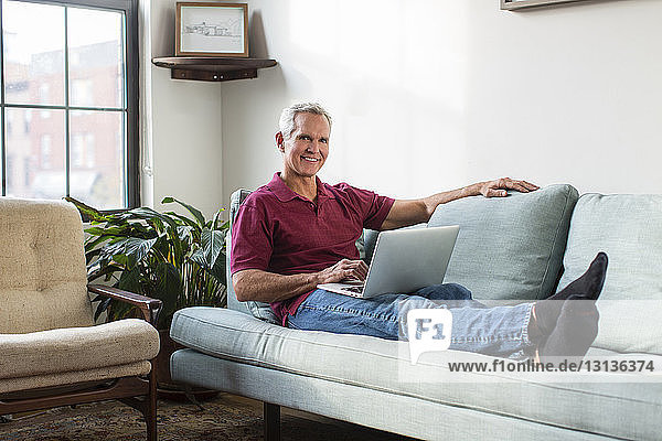 Full length portrait of mature man using laptop computer while resting on sofa in living room at home
