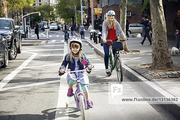 Portrait von Mutter und Tochter beim Fahrradfahren auf der Straße