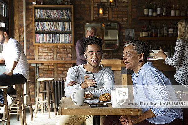 Lächelnder Mann zeigt Frau Telefon  während sich Kunden im Café entspannen