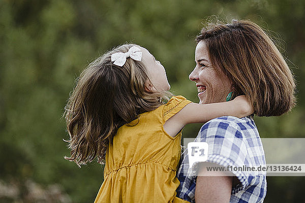 Cheerful mother and daughter against plants at field