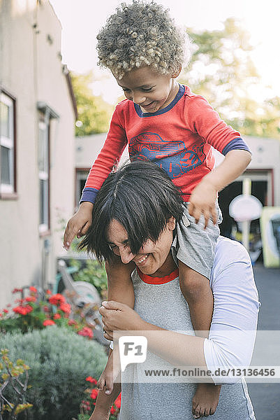 Glückliche Mutter trägt ihren Sohn auf den Schultern  während sie auf dem Fußweg steht
