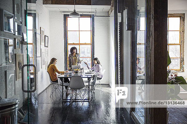Businesswomen discussing at table in creative office