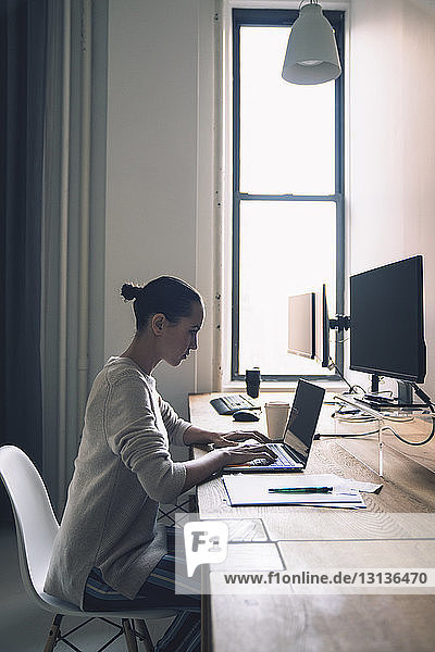 Side view of businesswoman using laptop computer while sitting at desk in office