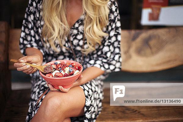 Mittelteil einer Frau  die zu Hause Frühstücksflocken isst