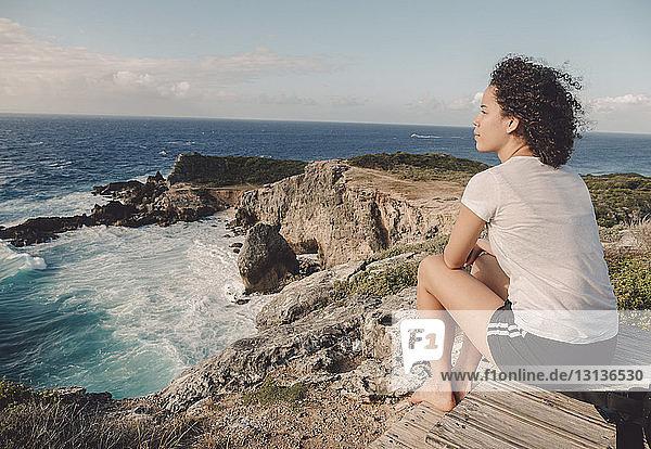 Seitenansicht einer Frau  die bei Sonnenuntergang auf einem Felsen am Strand gegen den Himmel sitzt