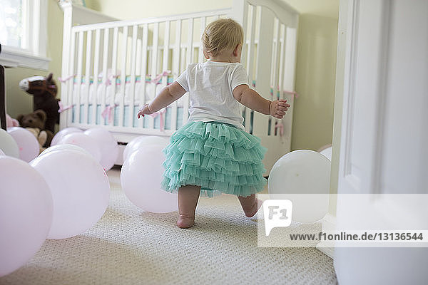 Rear view of baby girl playing with balloons at her first birthday party