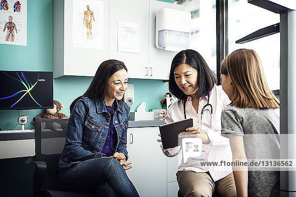 Glückliche Ärztin zeigt der Familie in der Klinik einen Tablet-Computer